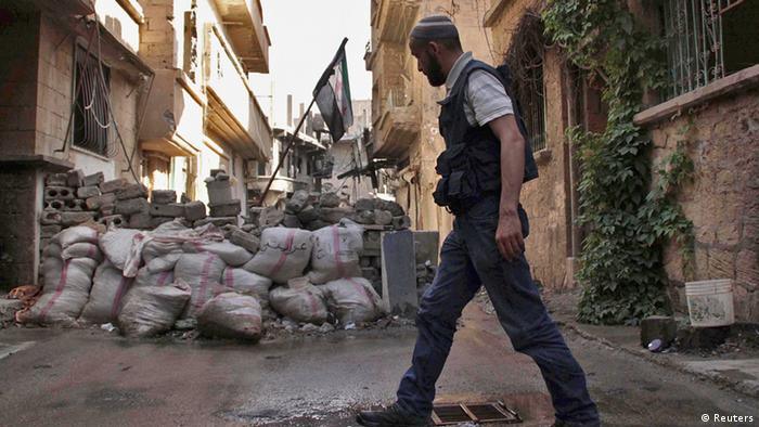 A Free Syrian Army fighter walks past a pile of sandbags with the Syrian opposition flag placed on it, in Deir al-Zor May 12, 2013. Picture taken May 12, 2013. REUTERS/Khalil Ashawi (SYRIA - Tags: CONFLICT CIVIL UNREST POLITICS)