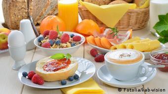 Ein gedeckter Frühstückstisch mit Kaffee, Brot, Wurst, Käse
