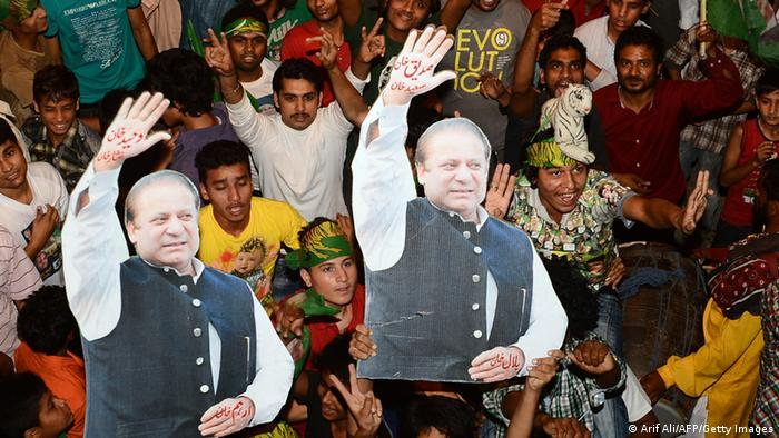 Supporters of former Pakistani Prime Minister and head of the Pakistan Muslim League-N (PML-N), Nawaz Sharif, carry portraits of Sharif as they celebrate the victory of their party a day after landmark general elections, in Lahore, on May 12, 2013. Pakistani election winner Nawaz Sharif was in talks today to form a new government, with fixing the shattered economy and tackling Islamist militancy likely to be his two biggest challenges. US President Barack Obama welcomed the 'historic, peaceful and transparent transfer of civilian power', saying Washington was ready to work 'as equal partners' with the new government. AFP PHOTO / ARIF ALI (Photo credit should read Arif Ali/AFP/Getty Images)