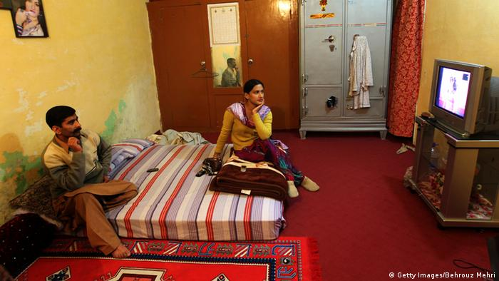 Pakistani eunuch Saba and her boyfriend Nasser (L) watch TV in her room in Rawalpindi on January 18, 2010. On the bottom rungs of Pakistan's social ladder, the eunuchs or Hijras scrape out a hard existence. Cultural descendants of the court eunuchs of the Mughal Empire (1526-1858), the eunuchs are often shunned by their families and forced to make a living by dancing, begging or as prostitutes (Foto: AFP PHOTO/BEHROUZ MEHRI).