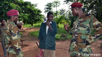 TO GO WITH AFP STORY BY PATRICK FORT Seleka rebel colonel Ali Garba (L) and his soldiers speak on April 7, 2013 with a man pretending to be a coalition rebel in Gondila, 65 kms north of Bangui. The alleged rebel holds in his hand an axe covered with a red cloth to make it look like a firearm. Seleka coalition leaders, who took power a month ago, are vowing to end looting, but achieving is a difficult task as in the countryside and in the capital Bangui, many looters are disguised as rebels and real rebels continue looting. AFP PHOTO / PATRICK FORT (Photo credit should read PATRICK FORT/AFP/Getty Images)
