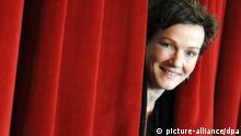 ARCHIV - Die künftige Intendantin des Deutschen Schauspielhauses, Karin Beier, schaut am 04.03.2011 zwischen einem Theatervorhang im Deutschen Schauspielhaus in Hamburg hervor. Zu ihrem Abschied als Intendantin des Kölner Schauspiels hat Karin Beier Euripides' «Troerinnen» inszeniert. Foto: Marcus Brandt/dpa (zu dpa «Intendantin Beier verabschiedet sich mit den «Troerinnen» aus Köln» vom 12.01.2013) +++(c) dpa - Bildfunk+++