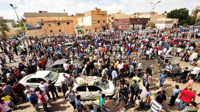 People gather at the scene of a car bomb explosion outside a hospital in Benghazi May 13, 2013. At least three people were killed and 17 wounded on Monday when the bomb exploded, a doctor at the hospital said. A second doctor said only one of the bodies had arrived intact, making it difficult to immediately establish the number killed. REUTERS/Esam Al-Fetori (LIBYA - Tags: CIVIL UNREST)
