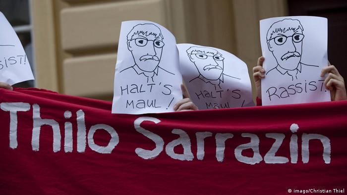 Caricatures of Thilo Sarazin held up over a red flag with the author's name and reading, Shut up! and Racist