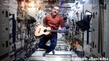 epa03698588 A handout video grabbed image made available by NASA showing CSA (Canadian Space Agency) astronaut Chris Hadfield performing aboard the International Space Station a revised version of David Bowie's song Space Oddity, 12 May 2013. As reported by CSA, Hadfield, for his last downlink before returning to Earth, CSA Astronaut Chris Hadfield performed I.S.S. (Is Somebody Singing) with hundreds of students at the Ontario Science Centre and nearly a million people, mostly students from coast-to-coast Canada and around the world, performing the song in unison from their location. US astronaut Thomas Marshburn and Canadian astronaut Chris Hadfield are due to return back to Earth later on 13 May 2013. EPA/NASA / CSA / CHRIS HADFIELD / HANDOUT HANDOUT EDITORIAL USE ONLY +++(c) dpa - Bildfunk+++