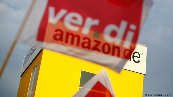 A flag of German united services union Ver.di is pictured in front of the logo of Amazon on a warehouse in Bad Hersfeld May 14, 2013. (Photo via REUTERS/Lisi Niesner)