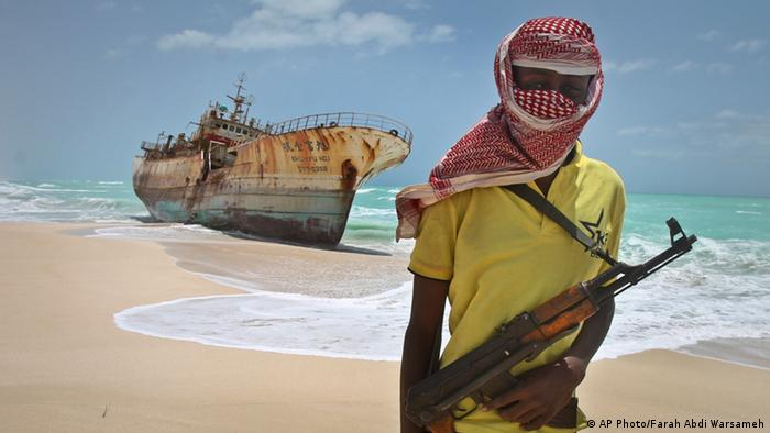 A masked Somali pirate stands near a Taiwanese fishing vessel on shore near Hobyo, Somalia (Photo: Farah Abdi Warsameh)