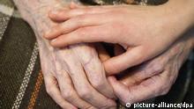 ARCHIV - Eine junge Pflegekraft hält am 29.11.2012 die Hände einer alten und demenzkranken Frau in einem Pflegeheim in Frankfurt (Oder) (Brandenburg). Die Bundesregierung will am 14.05.2013 bei ihrem zweiten Demografiegipfel über die Herausforderungen einer alternden Gesellschaft beraten. Foto: Patrick Pleul/dpa +++(c) dpa - Bildfunk+++