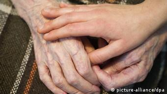 A caregiver's hand clasps an elderly person's hands Photo: Patrick Pleul/dpa +++(c) dpa - Bildfunk+++