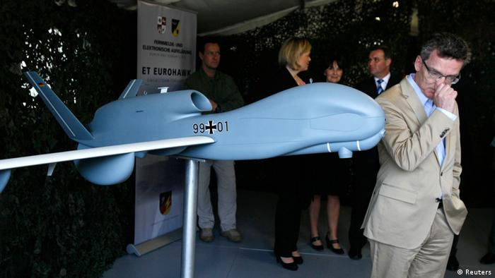 File picture shows German Defence Minister Thomas de Maiziere as he stands next to a model of the Euro Hawk unmanned aerial vehicle (UAV) during his visit to the Joint Support Service base in Grafschaft near the western German city of Bonn (Photo: Reuters)