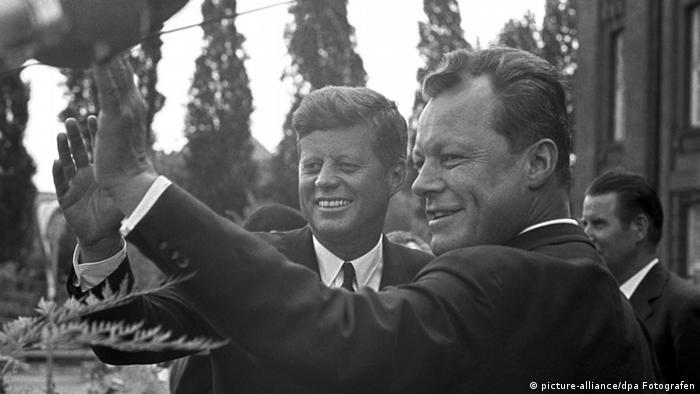 Präsident Kennedy (l) und Berlins Regierender Bürgermeister Willy Brandt (r) winken vor dem Rathaus Schöneberg der versammelten Menge zu - Foto: dpa