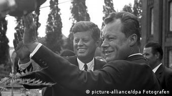 Präsident Kennedy (l) und Berlins Regierender Bürgermeister Willy Brandt (r) winken vor dem Rathaus Schöneberg der versammelten Menge zu. Der Besuch des amerikanischen Präsidenten John F. Kennedy am 26. Juni 1963 in Berlin gestaltete sich zu einem Triumphzug, dessen Höhepunkt das Kennedy-Bekenntnis Ich bin ein Berliner war.