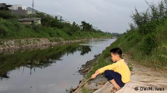 A boy squats beside a canal in Danang, a coastal city in central Vietnam. Developing countries do not have the same child-protection standards that developing countries do, such as protective fences that protect kids from potential water hazards.