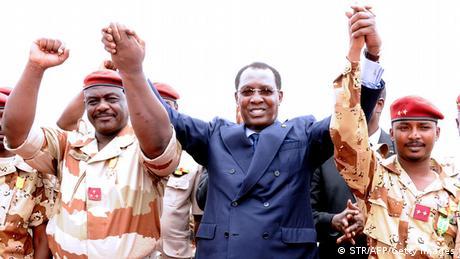 Le président Idriss Deby Itno tient les mains du général Oumar Bikimo (gauche) et de son fils Mahamat Idriss Deby lors d'une cérémonie à N'Djamena (13.05.2013)