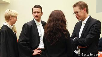 MUNICH, GERMANY - MAY 15: Lawyers Anja Sturm (L), Wolfgang Stahl (2L) and Wolfgang Heer (R) chat with their client Beate Zschaepe in the courtroom on day three of the NSU neo-Nazis murder trial at the Oberlandgericht Muenchen court on May 15, 2013 in Munich, Germany. Zschaepe is the main defendant and is on trial for her role in assisting Uwe Boehnhardt and Uwe Mundlos in the murder of nine immigrants and one policewoman across Germany between 2000 and 2007. Together the trio called themselves the NSU, or National Socialist Underground. Four other co-defendants, including Ralf Wohlleben, Holder G., Carsten S. and Andre E., are accused of assisting the trio. Zschaepe has thus far remained silent and has refused to answer any questions by the court, including when asked to state her name. (Photo by Johannes Simon/Getty Images)