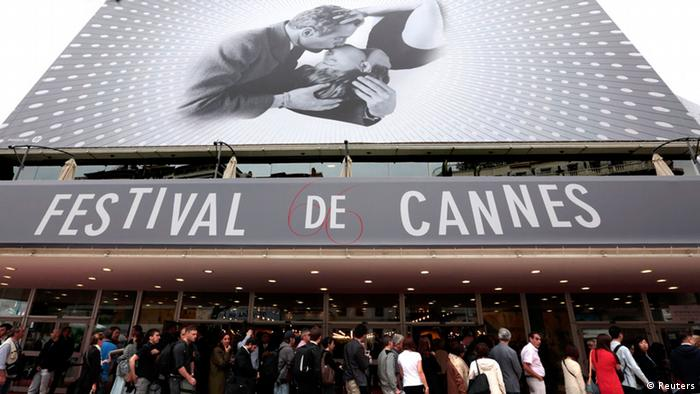 Visitors wait to enter in the Festival Palace covered by a giant canvas of the official poster of the 66th Cannes Film Festival in Cannes May 15, 2013. The 66th Cannes Film Festival will run from May 15 to May 26. REUTERS/Eric Gaillard (FRANCE - Tags: ENTERTAINMENT)
