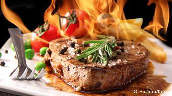 Ein Steak und Flammen im Hintergrund