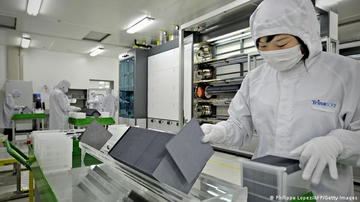 A masked worker in a lab coat sorting silicon wafers at the manufacturing centre of solar cell maker Trina Solar in Changzhou. (Photo: AFP)