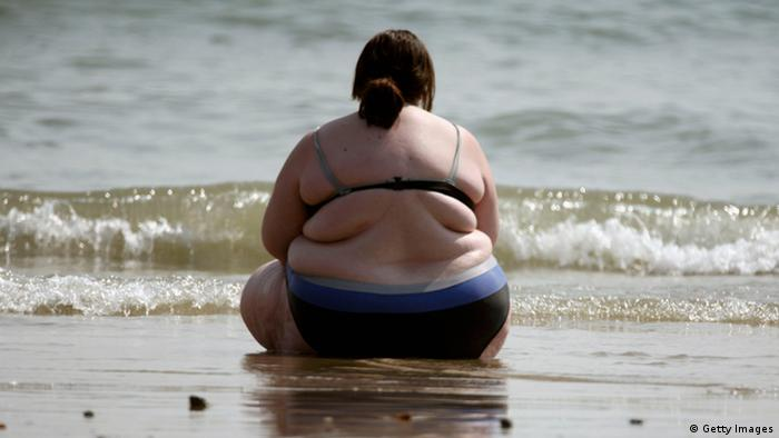An overweight woman sits on a beach on a dark English seashore (Photo: Matt Cardy/Getty Images)
