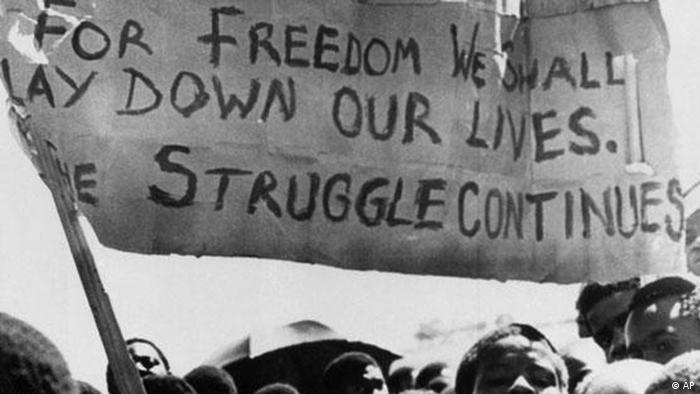 A banner is held aloft above black students in Johannesburg, South Africa, in the township of Soweto where they rallied after the funeral of a 16-year-old black student who died in jail, Oct. 18, 1976. The student, Dumisani Mbatha, who was arrested following a protest march last month by young blacks in Johannesburg, died two days after his arrest Sept. 23. (AP Photo)