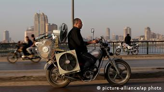 An Egyptian man transports electric fans, as ride his motorcycle on a bridge, in Cairo, Egypt, Friday, May 10, 2013. (AP Photo/Hassan Ammar)