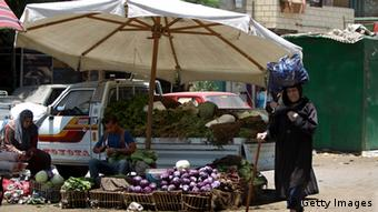 An elderly Egyptian woman walks in a market in Cairo 