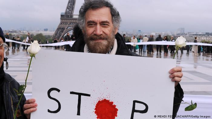 "Ali Ferzat holds a placard reading ""stop"""