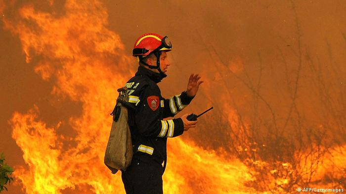 A fireman fights a wildfire near Vrpolje, close to Croatian mid-Adriatic touristic town of Sibenik, some 300 kilometers south of Zagreb, on July 23, 2012. Over 1,500 tourists were evacuated today and a firefighter died after several wildfires fanned by strong winds broke out on several places along the Croatia's Adriatic coast as the interior minister warned the situation was becoming serious. AFP PHOTO / STRINGER ***CROATIA OUT*** (Photo credit should read -/AFP/GettyImages)