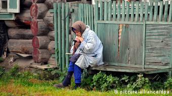 Пожилая женщина на лавочке возле дома в деревне