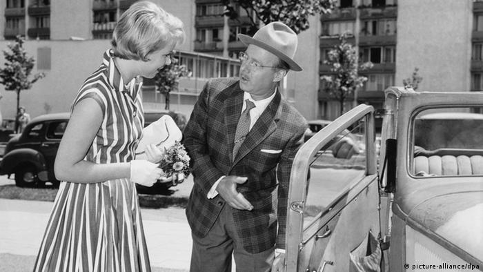 Filmszene aus Der Pauker: Heinz Rühmann (rechts) hält) seiner Filmpartnerin die Autotür auf