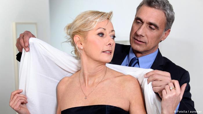 Ein Mann hilft einer Frau, ein Tuch umzulegen