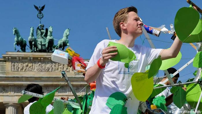 Summit participant hanging flyers on the 'Tree of Hope' in Berlin Photo: Ole Spata/dpa +++(c) dpa - Bildfunk+++