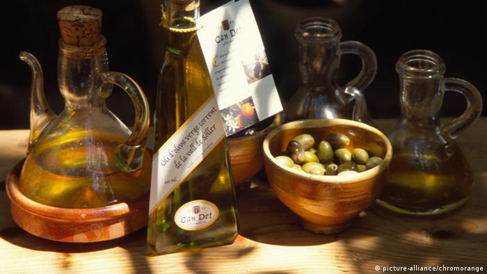 Olivenöl und Oliven stehen auf einem Tisch