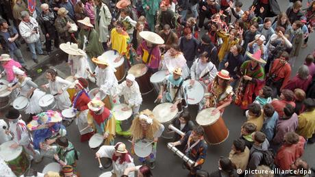 Parade-goers, many of them carrying drums, walk on a street below (Photo: ARCHIVBILD 1996)