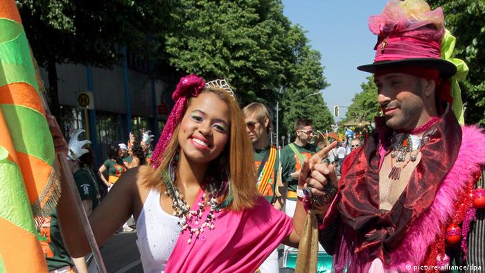 Wearing pink costumes, a woman and man parade down the street (Photo: Wolfgang Kumm/dpa)