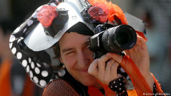 A woman wearing a bug hat takes a photograph with her camera (Photo: Wolfgang Kumm/dpa)