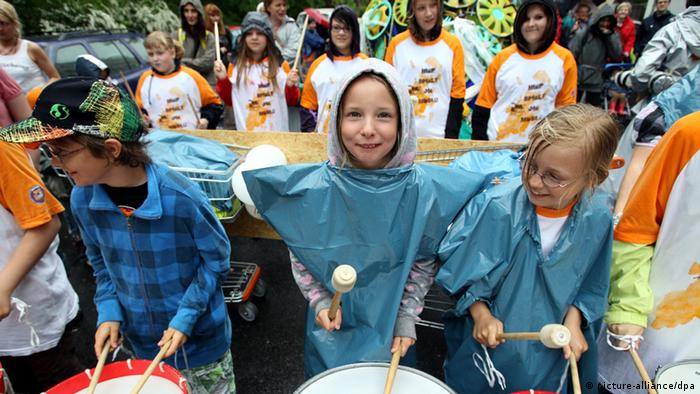 A group of children, some of whom are wearing blue plastic ponchos to protect from rain, beat drums as part of a large festival (Photo: Wolfgang Kumm/dpa)
