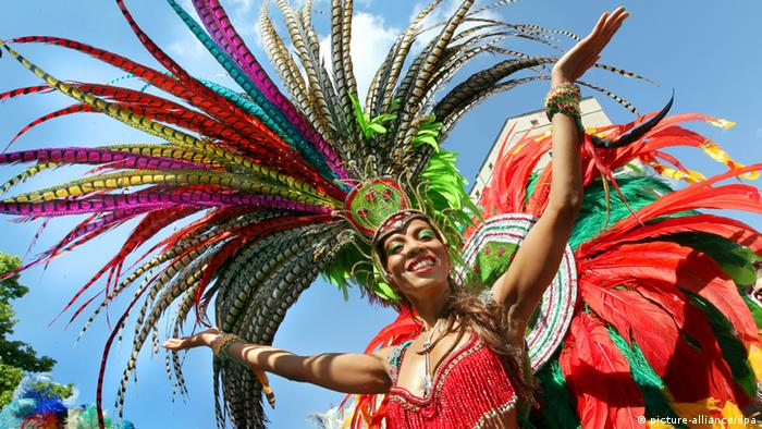 A woman wearing a garish hat made up of feathers spreads her arms and smiles. (Photo: Wolfgang Kumm/dpa)