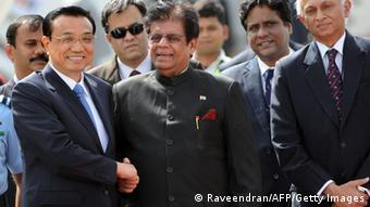 Chinese Premier, Li Keqiang (L) shakes hands with Indian Minister of State for External Affairs, E. Ahmed on his arrival at Palam Airport in New Delhi on May 19, 2013. Chinese Premier Li Keqiang arrived in India Sunday afternoon on the first stop of his maiden foreign trip, for talks on issues ranging from an unresolved border dispute to a festering trade-imbalance. AFP PHOTO/RAVEENDRAN (Photo credit should read RAVEENDRAN/AFP/Getty Images)
