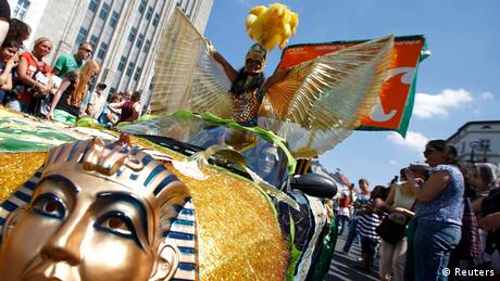 A woman whose costume includes golden wings rides atop a float with an image of the Egyptian sphynx on it (Photo: Pawel Kopczynski/Reuters