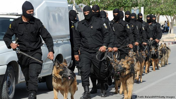 Tunisian Police Special Unit agents with dogs patrol in a street that leads to Okba Ibn Nafaa mosque in the central Tunisian city of Kairouan on May 19, 2013. Tunisian Salafist movement Ansar al-Sharia called on its supporters to gather in a Tunis suburb, after the government banned it from holding its annual congress in the central city of Kairouan. AFP PHOTO / FETHI BELAID (Photo credit should read FETHI BELAID/AFP/Getty Images)