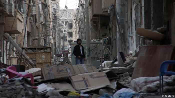 A man stands in a damaged street filled with rubble in Deir al-Zor, May 18, 2013. Picture taken May 18, 2013. REUTERS/Khalil Ashawi (SYRIA - Tags: POLITICS CIVIL UNREST CONFLICT)