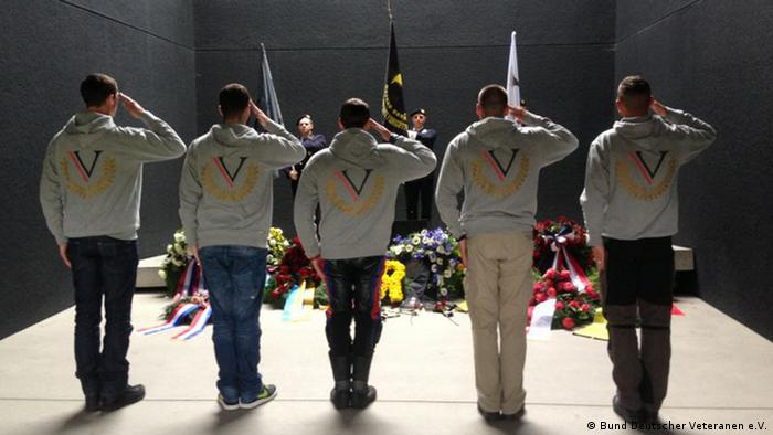 German veterans salute at a memorial