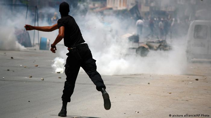 A Tunisian police officer clashes with radical Islamist movement Ansar al-Shariah supporters (photo: AP Photo/Nawfel)