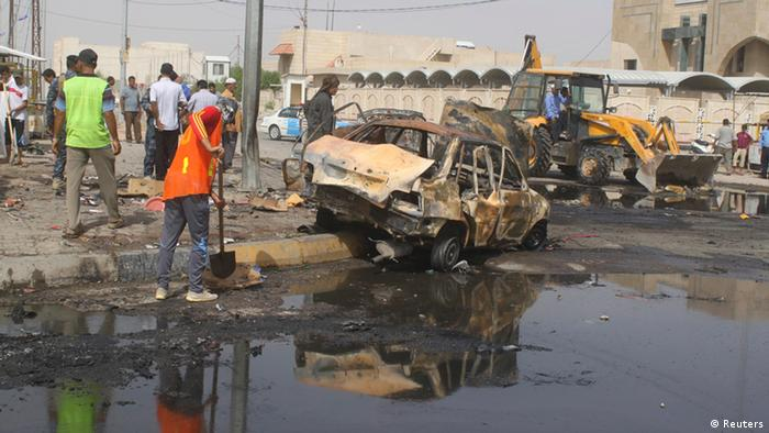 Municipality workers clean the site of a bomb attack in Basra, 420 km (260 miles) southeast of Baghdad, May 20, 2013. Two car bombs hit Basra, a predominantly Shi'ite southern city 420 km (260 miles) southeast of Baghdad. The first struck the Hananiya neighbourhood, near a busy market and restaurants, and the second was detonated inside a bus terminal in Saad Square, police and medics said. Eleven people were killed. REUTERS/Atef Hassan (IRAQ - Tags: CIVIL UNREST POLITICS)