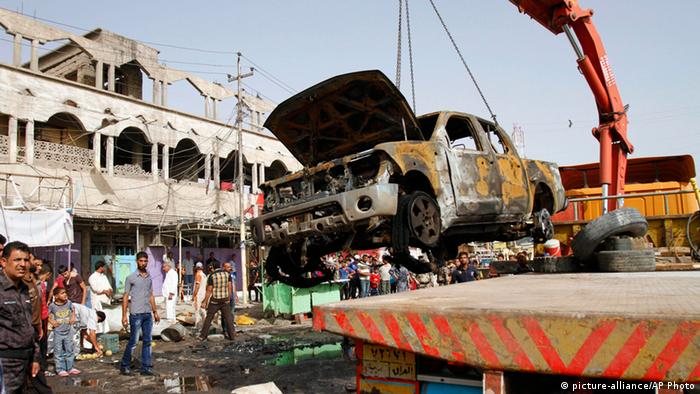 A wrecked truck is removed from the site of a car bomb attack in front of a crowded popular restaurant in Basra (AP Photo/ Nabil al-Jurani)