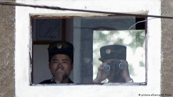 North Korean soldiers watch Chinese side from border town Simuiju, North Korea, as they are seen from Dandong, northeastern Liaoning province of China, Monday, May 20, 2013. North Korea fired a short-range projectile into its own eastern waters Monday for the fifth time in three days, Seoul officials said, as Pyongyang threatened to retaliate against any outside criticism of its rocket tests meant to bolster defense against what it calls U.S. and South Korean threats to attack. (AP Photo/Kyodo News) JAPAN OUT, MANDATORY CREDIT