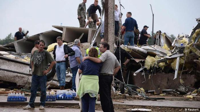 Residents and rescuers look over the damage after a tornado struck Moore, Oklahoma, May 20, 2013. REUTERS/Gene Blevins