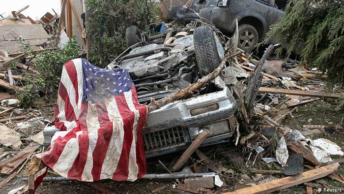 An American flag lies on top of an overturned car after a tornado struck Moore, Oklahoma, May 20, 2013. A 2-mile-wide (3-km-wide) tornado tore through the Oklahoma City suburb of Moore on Monday, killing at least 51 people while destroying entire tracts of homes, piling cars atop one another, and trapping two dozen school children beneath rubble. REUTERS/Gene Blevins (UNITED STATES - Tags: ENVIRONMENT DISASTER)