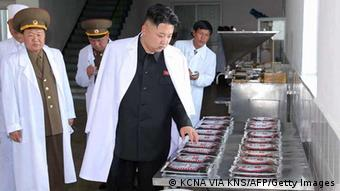 This undated picture, released from North Korea's official Korean Central News Agency (KCNA) on May 17, 2013 shows North Korean leader Kim Jong Un (C) inspecting the February 20 factory of the Korean People's Army (KPA), producing varieties of foodstuff at undisclosed place in North Korea. AFP PHOTO / KCNA